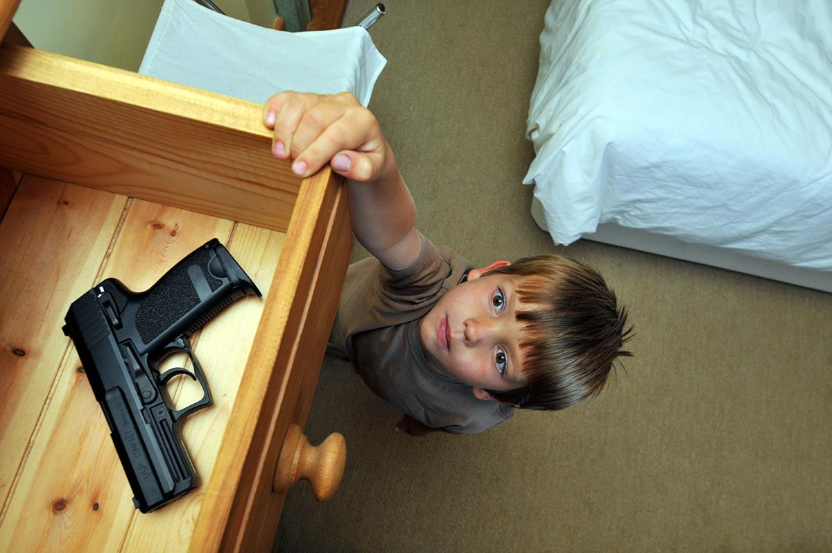 child looking up at drawer containing a gun