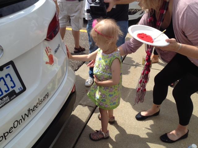 C.S. Mott Children's Hospital patient puts her handprint on a Hyundai Sonata.