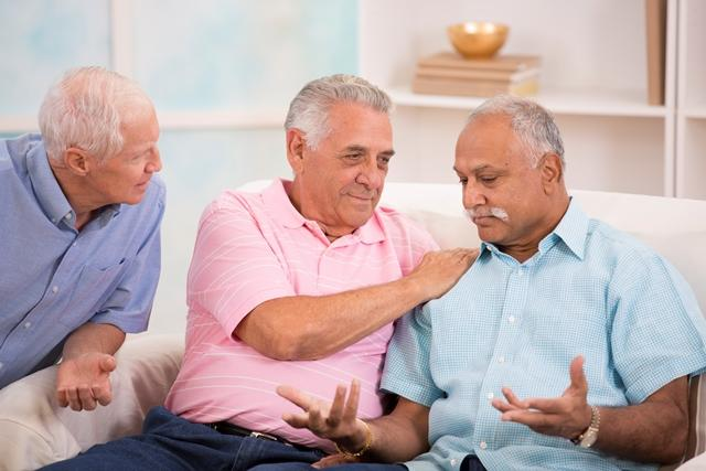 two men listen to a third man