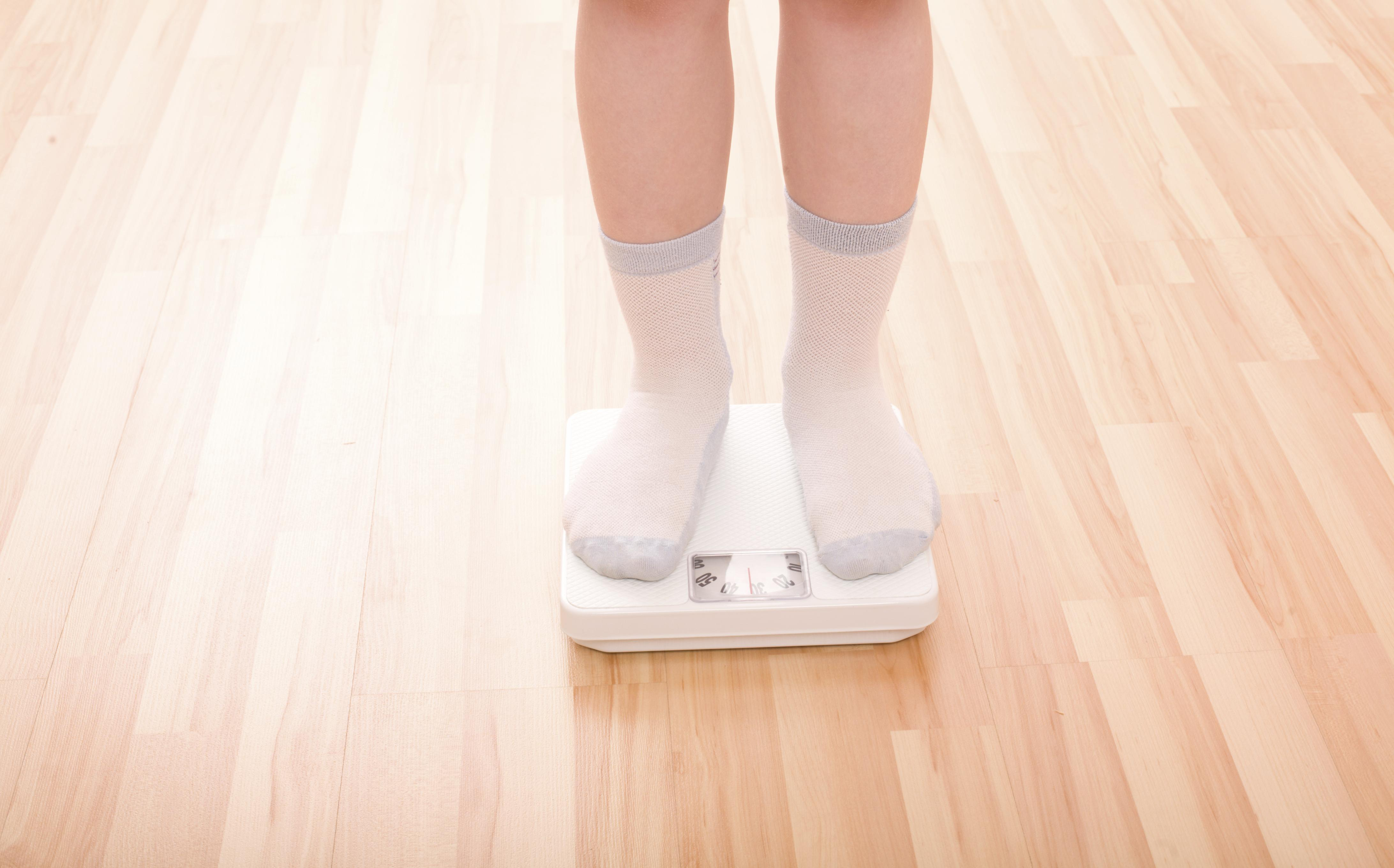 Child with feet on weight scale